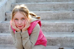 Photo of young girl sitting on steps by herself