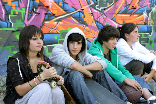 Photo of group of teenagers in front of graffiti wall